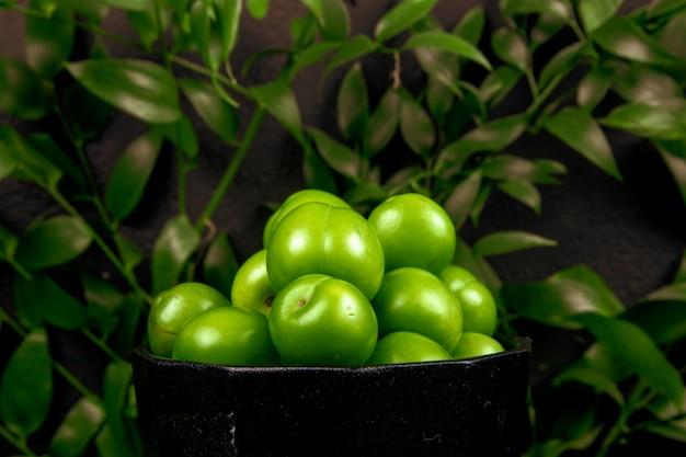 Vista lateral de ameixas verdes azedas em uma tigela na mesa de folhas verdes