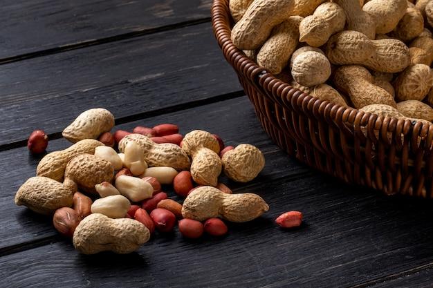 Vista lateral de amendoim com casca em uma cesta com descascado em uma mesa de madeira preta
