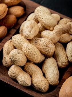 Vista lateral de amendoins com casca em uma bandeja de madeira