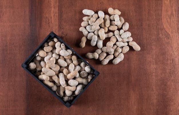 Vista lateral de amendoins em caixa na vertical de madeira