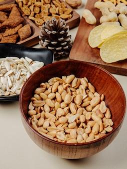 Vista lateral de amendoins salgadinhos em uma tigela de madeira com vários lanches para cerveja na mesa