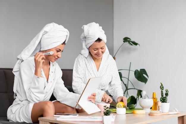 Vista lateral de amigas aplicando produtos de beleza