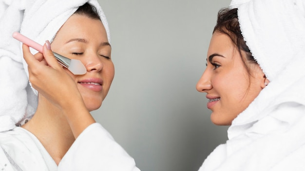 Vista lateral de amigas aplicando produtos para a pele