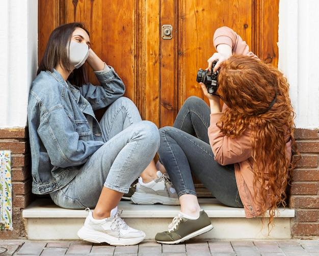 Vista lateral de amigas com máscaras sentadas ao lado da porta tirando fotos com a câmera
