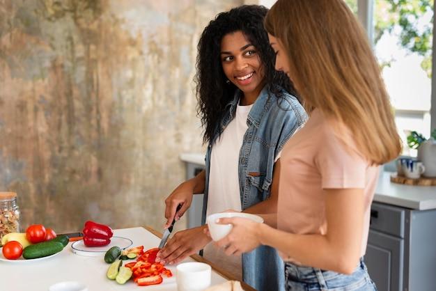 Vista lateral de amigas cozinhando juntas na cozinha