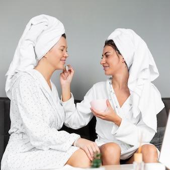 Vista lateral de amigas se ajudando nos cuidados da pele