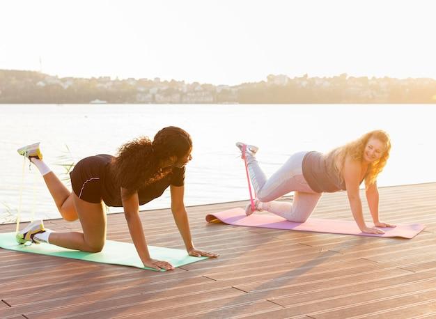 Vista lateral de amigas treinando juntas à beira do lago