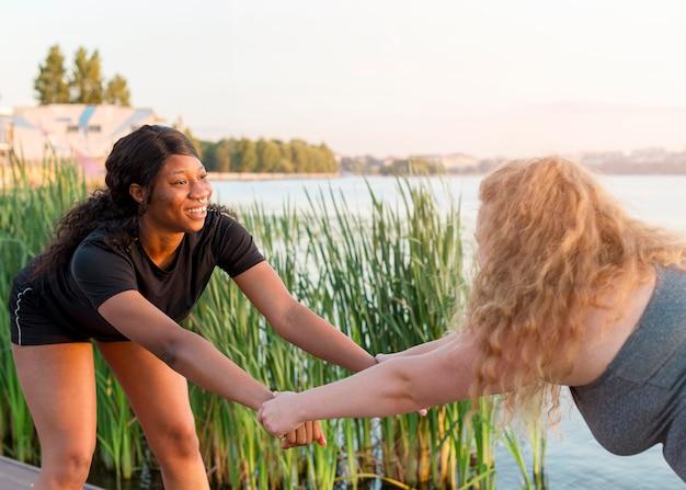 Vista lateral de amigas treinando juntas ao ar livre
