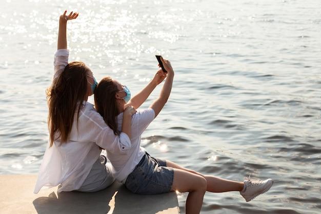 Vista lateral de amigos com máscaras médicas tirando selfie à beira do lago