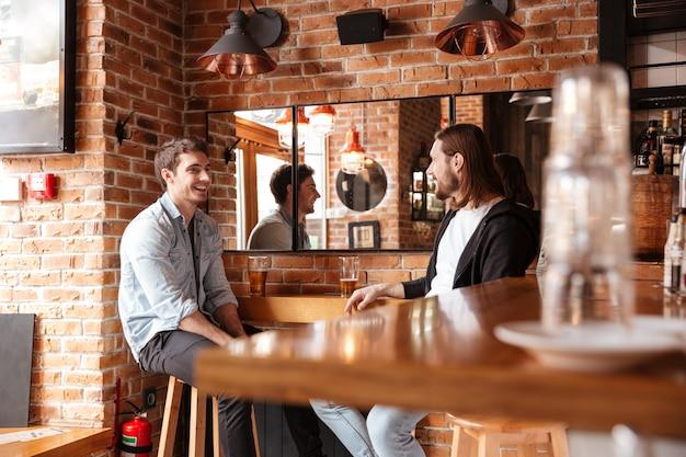 Vista lateral de amigos no bar perto do espelho