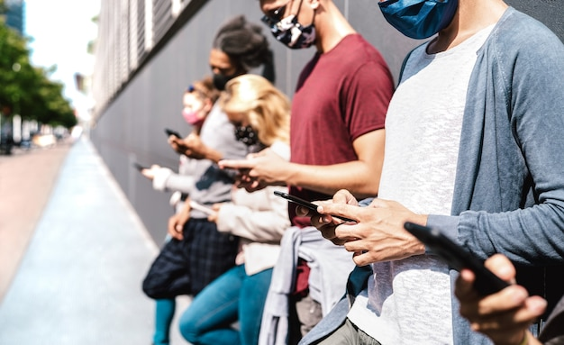 Vista lateral de amigos usando telefone celular coberto por máscara facial