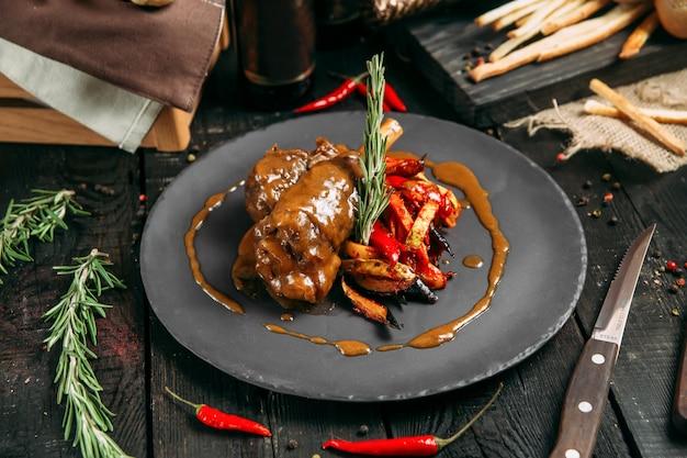 Vista lateral de apetitosa vitela cozida em molho com legumes em uma placa preta sobre um fundo escuro de madeira