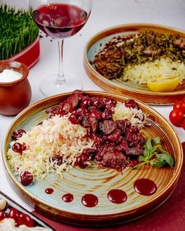 Vista lateral de arroz cozido com carne e cerejas