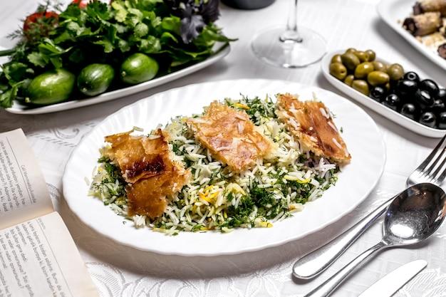 Vista lateral de arroz cozido com ervas e uma crosta com ervas e azeitonas