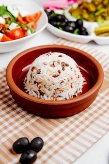 Vista lateral de arroz cozido com feijão em uma tigela de madeira