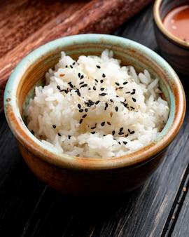 Vista lateral de arroz cozido com sementes pretas em uma tigela de barro na madeira