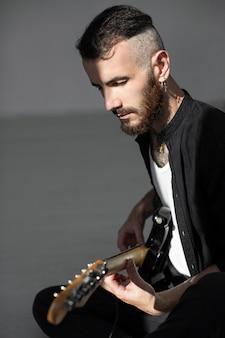 Vista lateral de artista masculino tocando guitarra elétrica