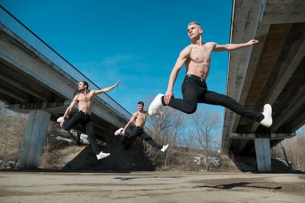 Vista lateral de artistas de hip hop sem camisa dançando no ar