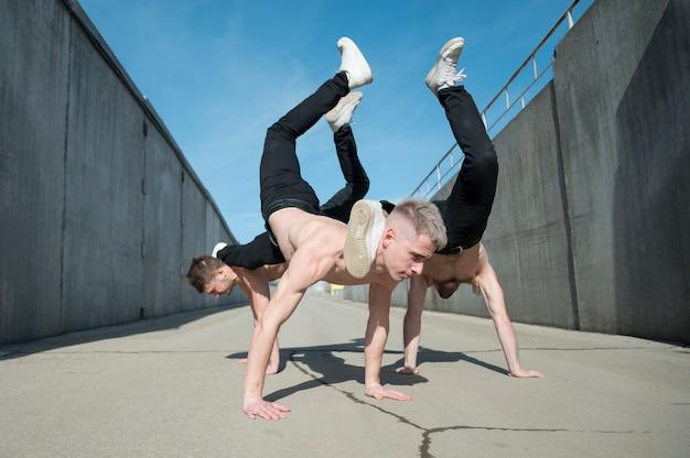 Vista lateral de artistas de hip-hop sem camisa dançando