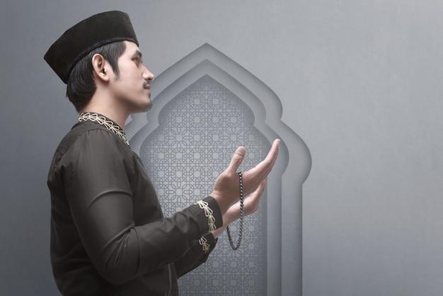 Vista lateral, de, asiático, muçulmano, macho, levantamento, mão, enquanto, orando