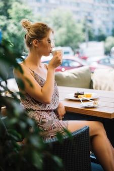 Vista lateral, de, atraente, mulher jovem, café bebendo, em, caf���