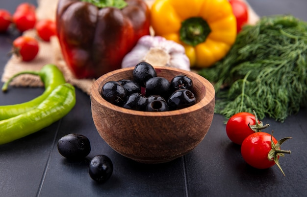 Vista lateral de azeitonas pretas em uma tigela com pimenta alho bulbo tomate e monte de endro ao redor na superfície preta