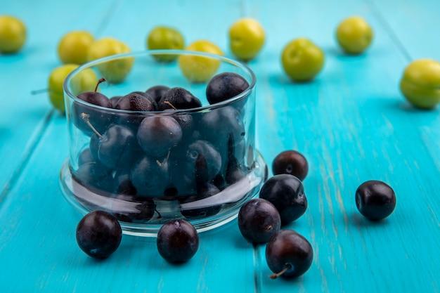 Vista lateral de bagas de uvas pretas em uma tigela e padrão de ameixas e bagas de uvas no fundo azul