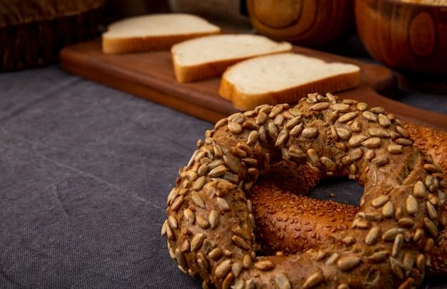 Vista lateral de bagels turcos com pão branco fatiado em fundo marrom com espaço de cópia
