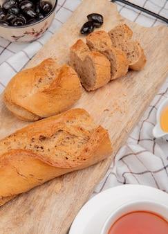 Vista lateral de baguete preta cortada e cortada com xícara de manteiga de chá no pano xadrez