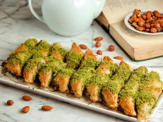Vista lateral de baklava de doces turcos com pistache na bandeja