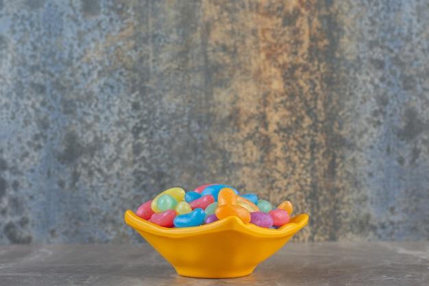 Vista lateral de balinhas coloridas em uma tigela laranja.