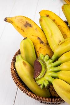 Vista lateral de bananas maduras frescas em uma cesta de vime em madeira branca