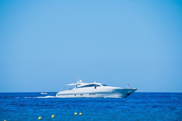 Vista lateral, de, barco vela, cruzando, em, mar azul
