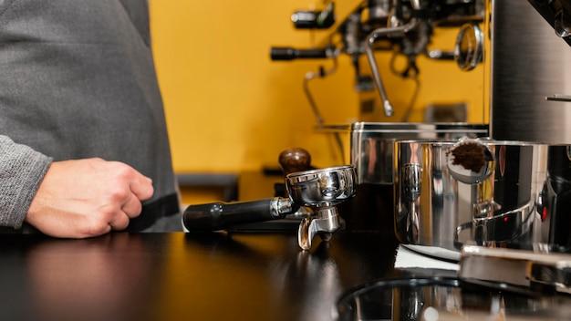 Vista lateral de barista com avental ao lado da máquina de café
