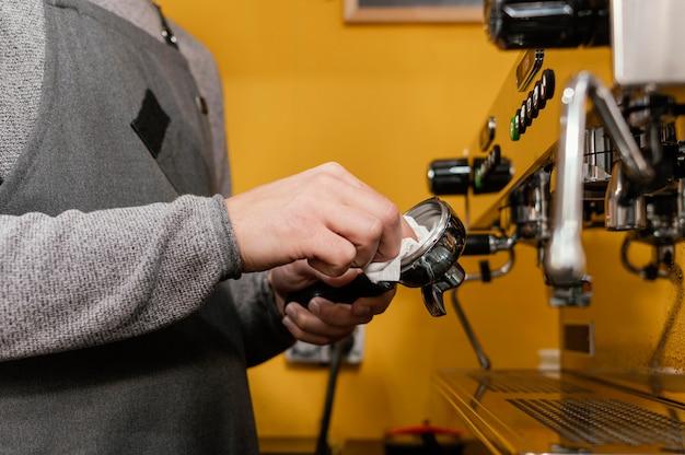Vista lateral de barista masculino com avental para limpeza de máquina de café profissional