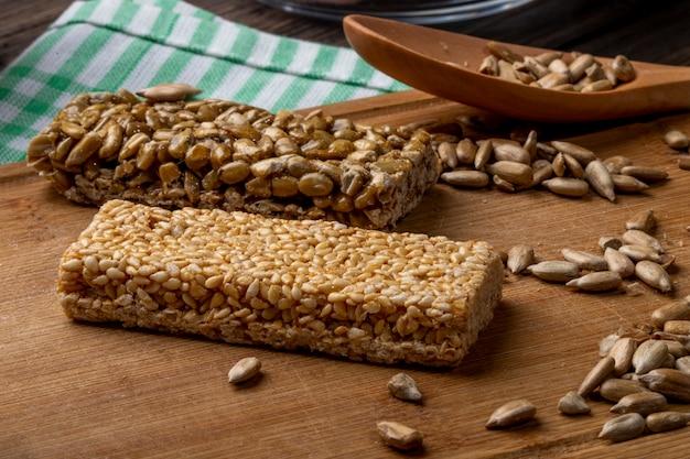 Vista lateral de barras de mel com amendoim e gergelim em uma placa de madeira rústica