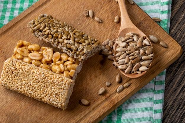 Vista lateral de barras de mel com amendoim gergelim e sementes de girassol em uma placa de madeira rústica