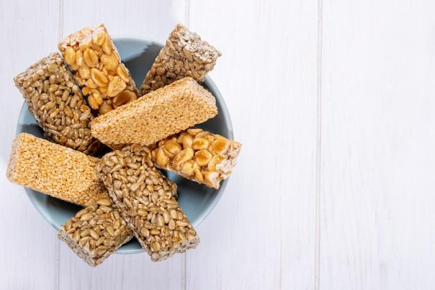Vista lateral de barras de mel com amendoim gergelim e sementes de girassol em uma tigela em branco