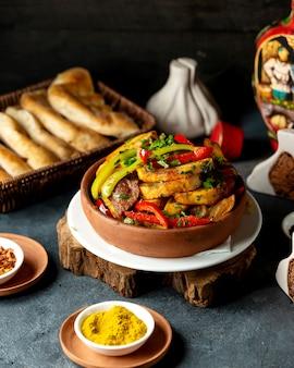 Vista lateral de batatas assadas com carne de cordeiro e legumes em uma tigela de barro em cima da mesa preta