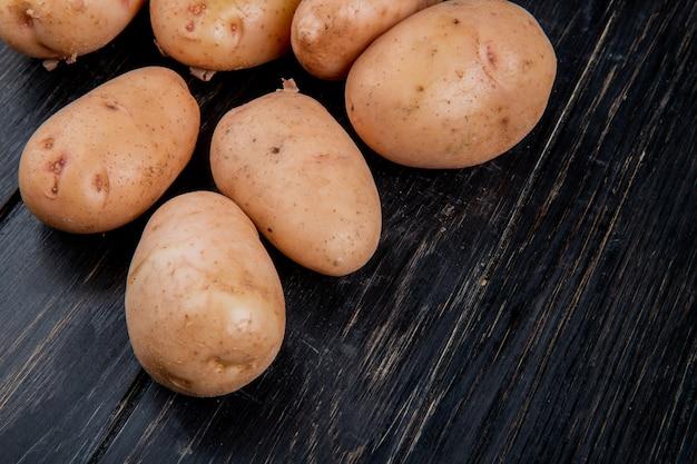 Vista lateral de batatas brancas na mesa de madeira