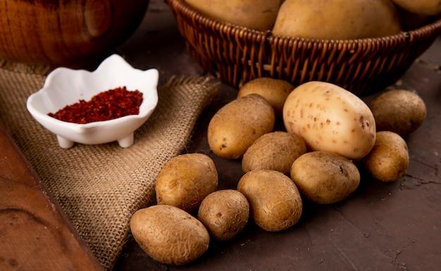 Vista lateral de batatas cruas com flocos de pimenta no fundo marrom