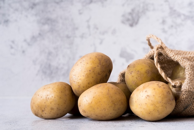 Vista lateral de batatas em saco de pano