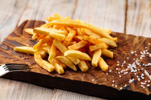 Vista lateral de batatas fritas com sal