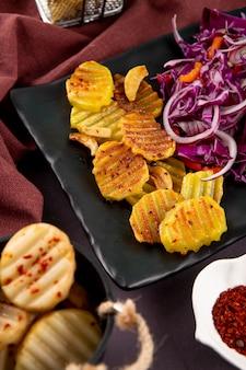 Vista lateral de batatas grelhadas com cebola roxa, repolho vermelho, pimentão laranja e flocos de pimenta seca em fundo cinza escuro