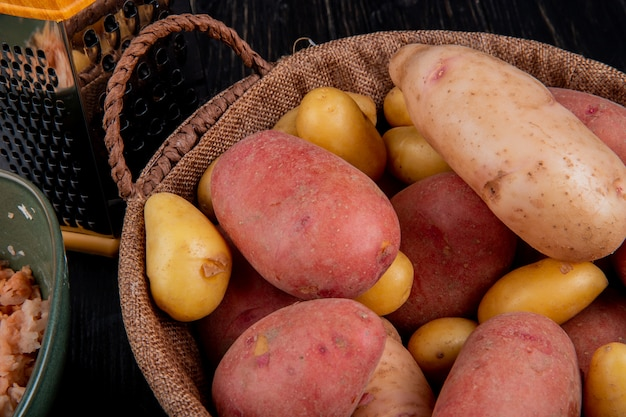 Vista lateral de batatas na cesta com ralador e batatas raladas em tigela na mesa de madeira