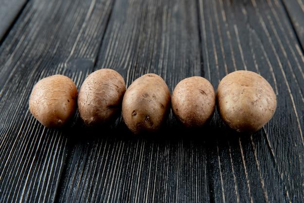 Vista lateral de batatas no fundo de madeira com espaço de cópia 4