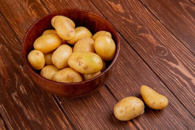 Vista lateral de batatas novas em uma tigela na mesa de madeira