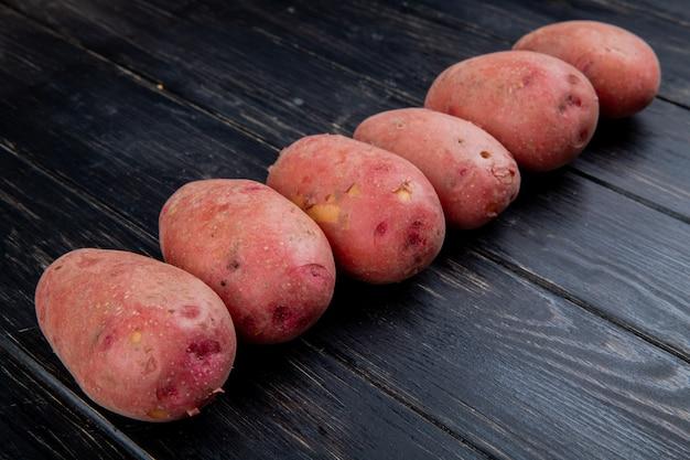Vista lateral de batatas vermelhas na mesa de madeira