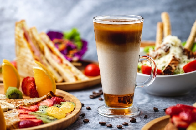 Vista lateral de bebida quente com café leite mel e grãos de café na mesa