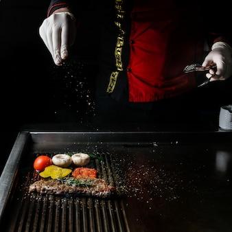Vista lateral de bife grelhado com alecrim e tomate e mãos humanas no churrasco